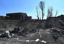 Burnt out houses and burnt trees are seen following a fire in Bormes-les-Mimosas, southeastern France, on July 26, 2017. At least 10,000 people, including thousands of holidaymakers, were evacuated overnight after a new wildfire broke out in southern France, which was already battling massive blazes, authorities said on July 26. / AFP PHOTO / Anne-Christine POUJOULAT